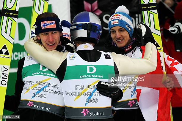 Thomas Morgenstern of Austria celebrates winning the gold medal with teammates Martin Koch and Gregor Schlerenzauer in the Men's Ski Jumping Team...