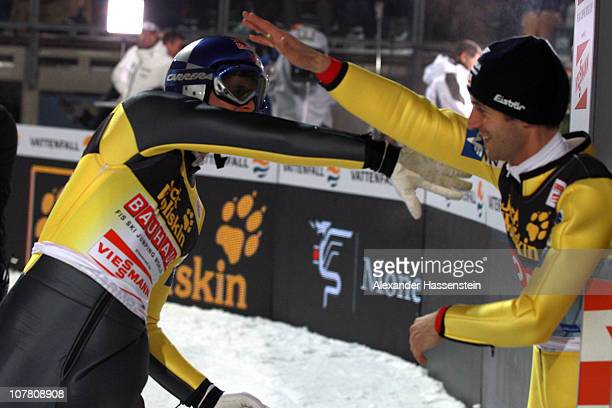 Thomas Morgenstern of Austria celebrates with his team mate Andreas Kofler after his final round jump during the FIS Ski Jumping World Cup event at...