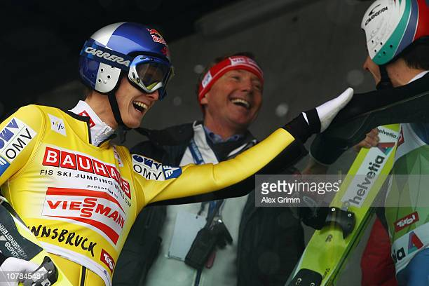 Thomas Morgenstern of Austria laughs with Walter Hofer, FIS race director, and Simon Ammann of Switzerland arrives for the training for the FIS Ski...