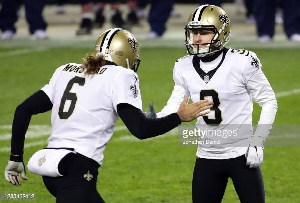 Thomas Morstead and Wil Lutz of the New Orleans Saints celebrate the game winning field goal against the Chicago Bears in overtime at Soldier Field...