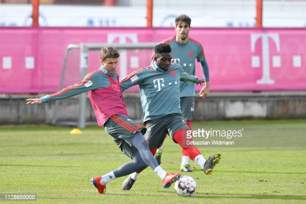 Thomas Mueller and Alphonso Davies of Bayern Munich compete for the ball during a FC Bayern Muenchen training session at Saebener Strasse training...