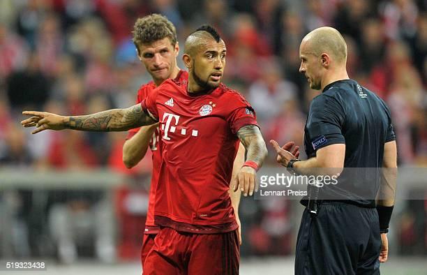 Thomas Mueller and Arturo Vidal of Bayern Muenchen talk to referee Szymon Marciniak during the UEFA Champions League Quarter Final first leg match...