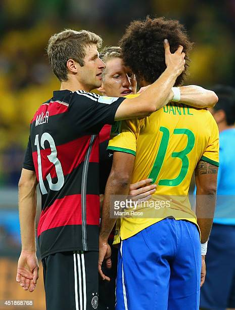 Thomas Mueller and Bastian Schweinsteiger of Germany console Dante of Brazil after Germany's 71 win during the 2014 FIFA World Cup Brazil Semi Final...