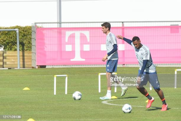 Thomas Mueller and Jerome Boateng of Bayern Muenchen plays the ball during a training session at Saebener Strasse training ground on April 06 2020 in...