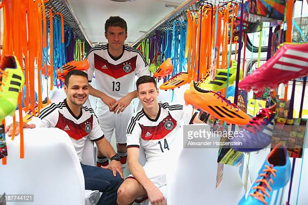 Thomas Mueller and Julian Draxler of the German national football team surprises the crowd with the new adidas Germany 2014 World Cup home kit during...
