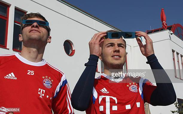 Thomas Mueller and Mario Goetze of Bayern Muenchen watch a penumbral solar eclipse before a training session at the FC Bayern Muenchen training...