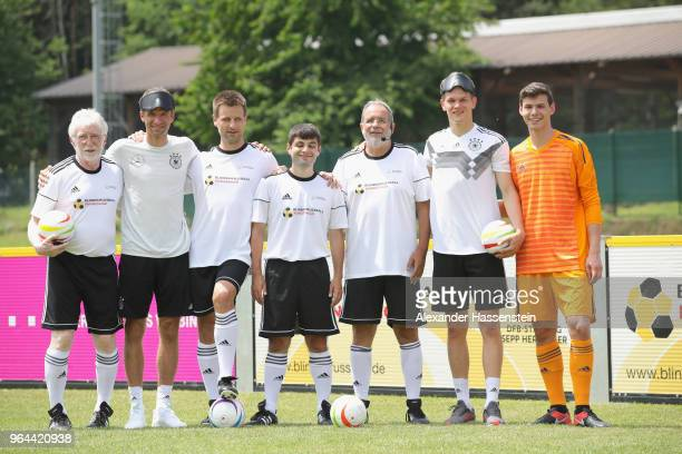 Thomas Mueller and Matthias Ginter 2nd R attend a Blind Football demonstration match with national players of the German national Blind Football team...