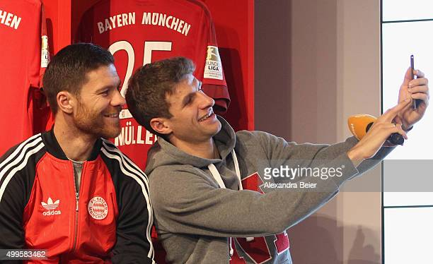Thomas Mueller and Xabi Alonso of FC Bayern Muenchen make a photograph with their new Gigaset ME mobile telephone during the handover to the players...