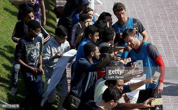 Thomas Mueller and Xavi Alonso are seen with fans after a training session at day 5 of the Bayern Muenchen training camp at Aspire Academy on January...