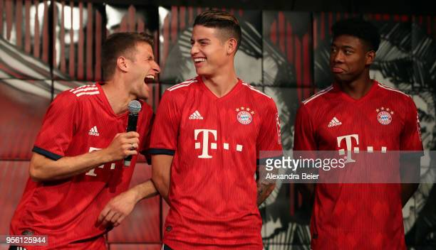 Thomas Mueller James Rodriguez and David Alaba of FC Bayern Muenchen joke wearing their new unveiled Adidas home jersey for the upcoming Bundesliga...