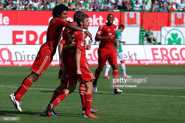 Thomas Mueller of Bayern celebrates the first goal with Dante during the Bundesliga match between Greuther Fuerth and FC Bayern Muenchen at Trolli...
