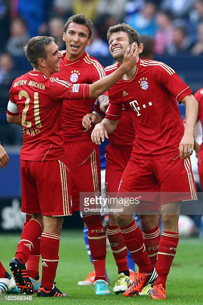 Thomas Mueller of Bayern celebrates the second goal with Philipp Lahm and Mario Mandzukic during the Bundesliga match between FC Schalke 04 and FC...