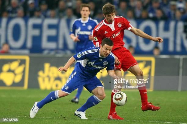 Thomas Mueller of Bayern challenges Alexander Baumjohann of Schalke during the DFB Cup semi final match between FC Schalke 04 and FC Bayern Muenchen...