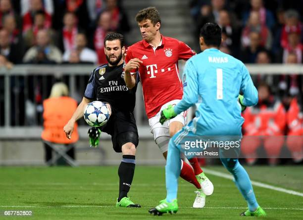 Thomas Mueller of Bayern is challenged by Nacho of Real Madrid during the UEFA Champions League Quarter Final first leg match between FC Bayern...