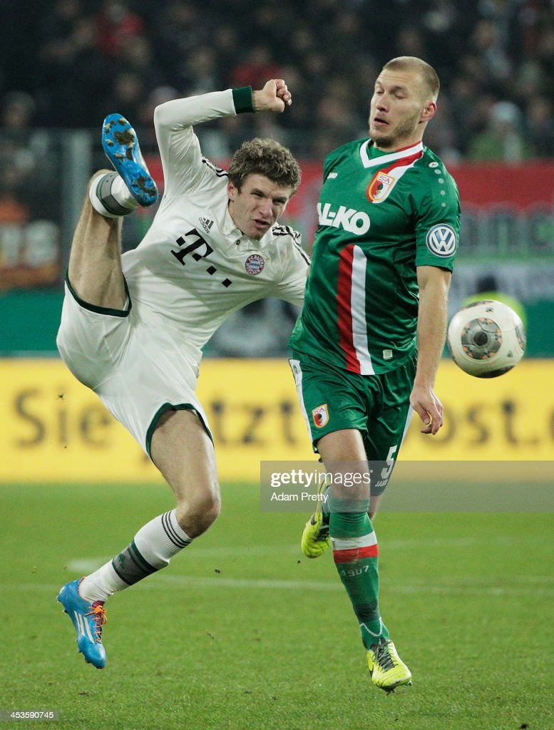 Thomas Mueller of Bayern is challenged by Ragnar Klavan of Augsburg during the FC Augsburg v Bayern Muenchen DFB Cup match at SGL Arena on December 4, 2013 in Augsburg, Germany.