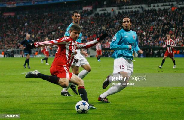 Thomas Mueller of Bayern Muenchen battles for the ball with Ionut Rada and Felice Piccolo of Cluj during the UEFA Champions League group E match...