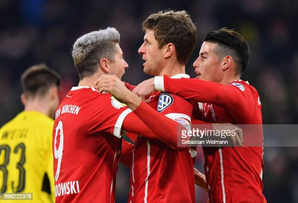 Thomas Mueller of Bayern Muenchen celebrates after scoring his sides second goal with Robert Lewandowski of Bayern Muenchen and James Rodriguez of...