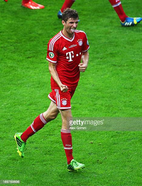 Thomas Mueller of Bayern Muenchen celebrates as he scores their first goal from the penalty spot during the DFB Cup Final match between FC Bayern...