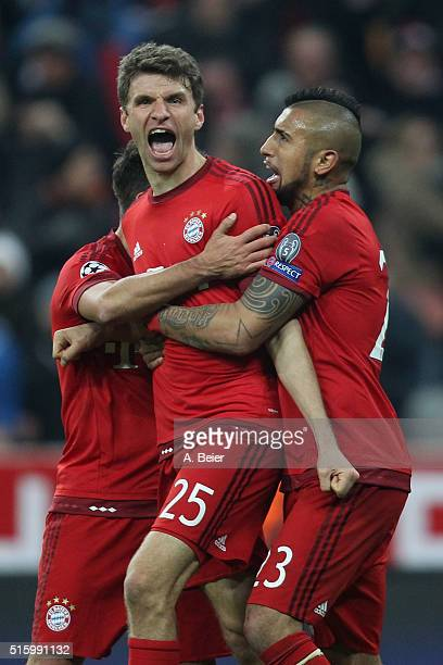 Thomas Mueller of Bayern Muenchen celebrates his first goal with teammates Juan Bernat and Arturo Vidal during the Champions League round of 16...