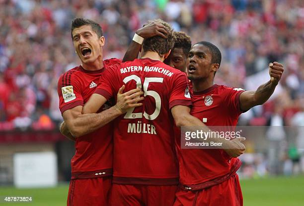 Thomas Mueller of Bayern Muenchen celebrates his penalty goal with teammates Robert Lewandowski David Alaba and Douglas Costa during the Bundesliga...