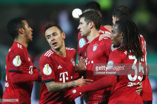 Thomas Mueller of Bayern Muenchen celebrates scoring his teams first goal of the game after he takes and scores a penalty with Rafinha Thiago...