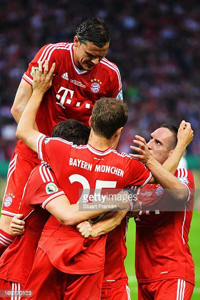 Thomas Mueller of Bayern Muenchen celebrates with team mates as he scores their first goal from the penalty spot during the DFB Cup Final match...