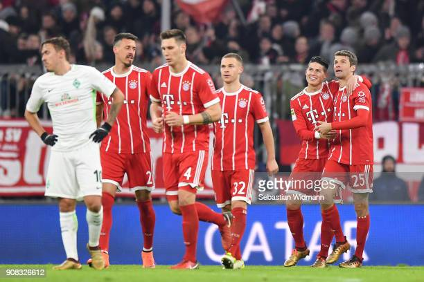 Thomas Mueller of Bayern Muenchen celebrates with teammate James Rodriguez scoring his teams fourth goal during the Bundesliga match between FC...