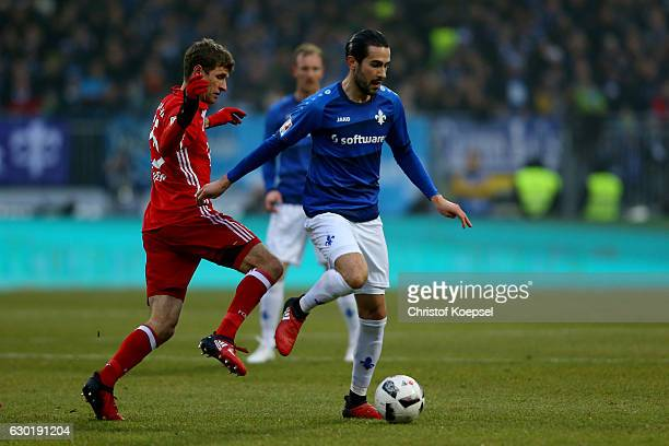 Thomas Mueller of Bayern Muenchen challenges Mario Vrancic of Darmstadt during the Bundesliga match between SV Darmstadt 98 and Bayern Muenchen at...
