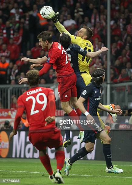 Thomas Mueller of Bayern Muenchen heads for the ball with goalkeeper Jan Oblak of Atletico Madrid during the Champions League semi final second leg...