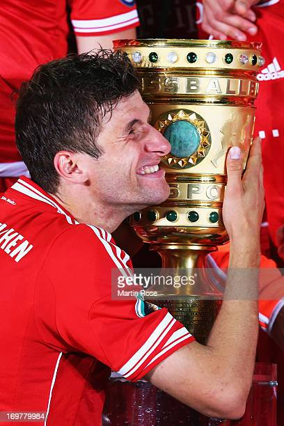 Thomas Mueller of Bayern Muenchen hugs the trophy to celebrate victory after the DFB Cup Final match between FC Bayern Muenchen and VfB Stuttgart at...
