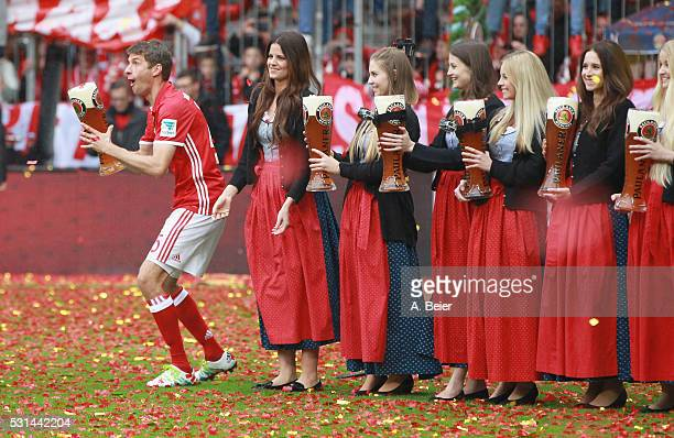 Thomas Mueller of Bayern Muenchen jokes with a beer mug during the German Championship celebration after the Bundesliga match between FC Bayern...