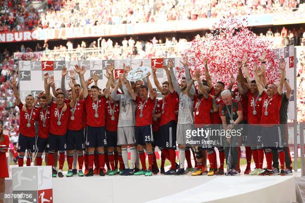 Thomas Mueller of Bayern Muenchen lifts the Bundesliga champions trophy after the Bundesliga match between FC Bayern Muenchen and VfB Stuttgart at...
