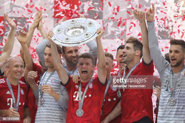 Thomas Mueller of Bayern Muenchen lifts the trophy in Celebration for winning the German Champiosnhip title after the Bundesliga match between FC...