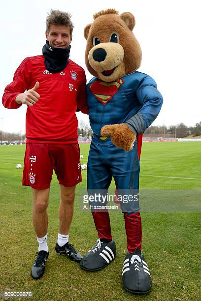 Thomas Mueller of Bayern Muenchen poses with mascot Bernie dressed as Superman prior to a training session at Bayern Muenchen's training ground...