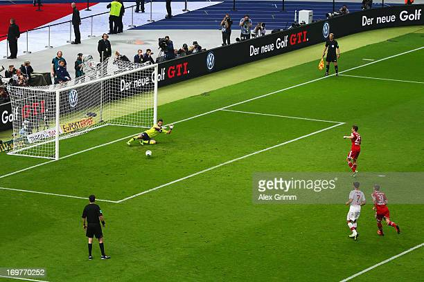 Thomas Mueller of Bayern Muenchen scores their first goal from the penalty spot past goalkeeper Sven Ulreich of VfB Stuttgart during the DFB Cup...