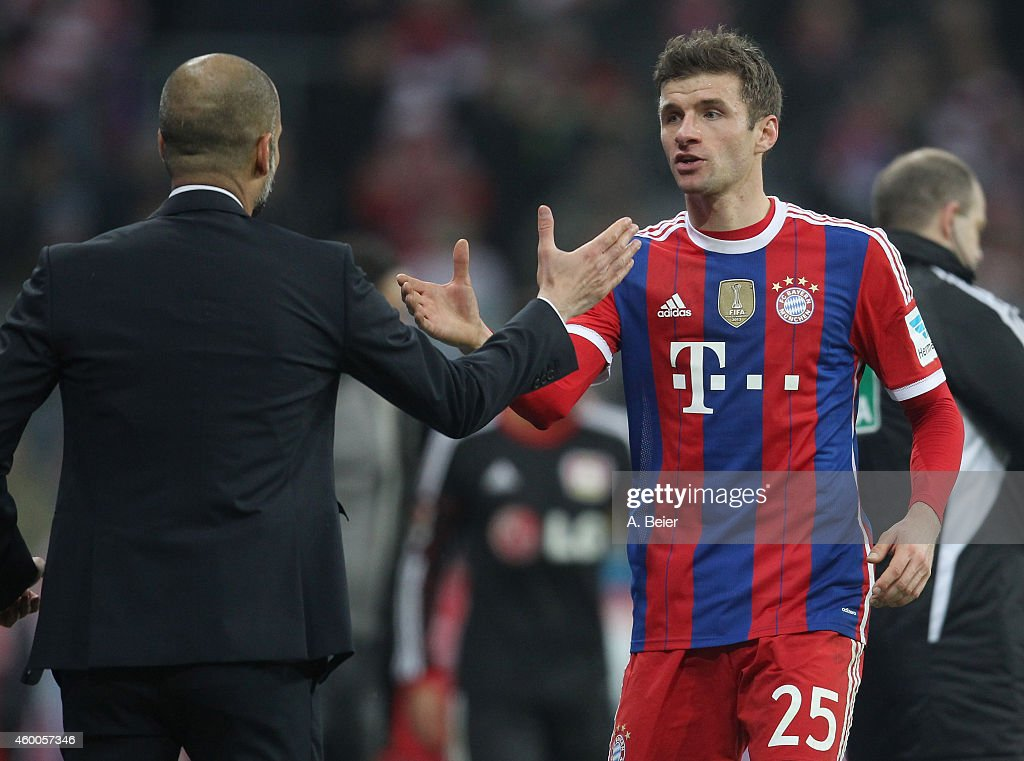 Thomas Mueller (R) of Bayern Muenchen shakes hands with team coach Josep Guardiola during the Bundesliga match between FC Bayern Muenchen and Bayer 04 Leverkusen at Allianz Arena on December 6, 2014 in Munich, Germany.