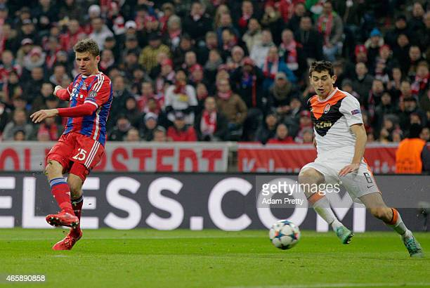 Thomas Mueller of Bayern Muenchen shoots past Taras Stepanenko of Shakhtar Donetsk as he scores their fourth goal during the UEFA Champions League...