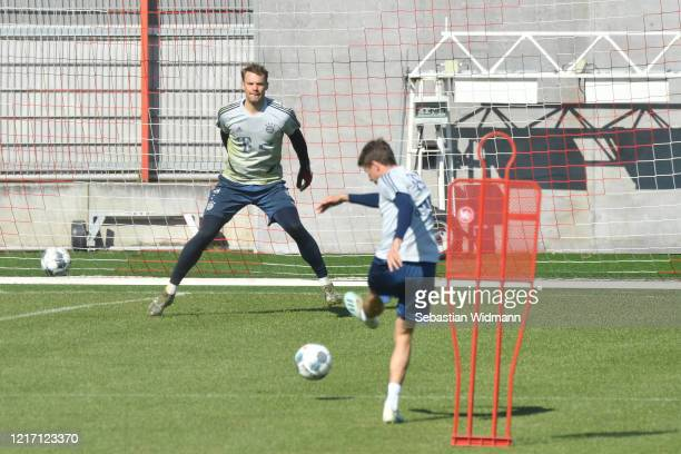 Thomas Mueller of Bayern Muenchen takes a shot at goalkeeper Manuel Neuer during a training session at Saebener Strasse training ground on April 06...