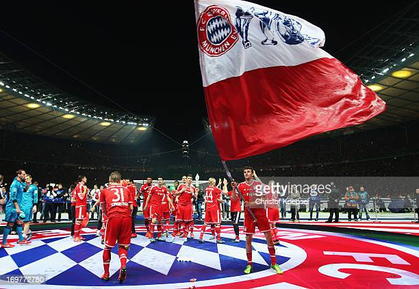 Thomas Mueller of Bayern Muenchen waves a flag as he celebrates victory with theam mates after the DFB Cup Final match between FC Bayern Muenchen and...