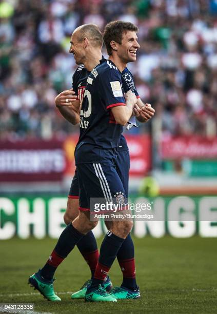 Thomas Mueller of Bayern Munich celebrates with Arjen Robben of Bayern Munich as he is substituted during the Bundesliga match between FC Augsburg...