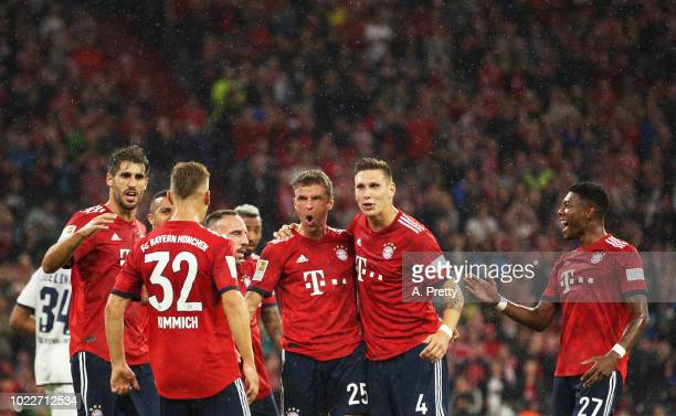 Thomas Mueller of Bayern Munich celebrates with David Alaba and Niklas Suele after scoring the first goal during the Bundesliga match between FC...