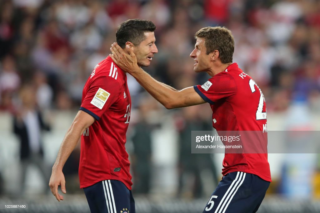 Thomas Mueller of Bayern Munich celebrates with teammate Robert Lewandowski after scoring his team's third goal during the Bundesliga match between VfB Stuttgart and FC Bayern Muenchen at Mercedes-Benz Arena on September 1, 2018 in Stuttgart, Germany.