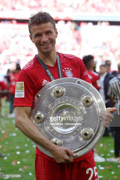 Thomas Mueller of Bayern Munich celebrates with the trophy following the Bundesliga match between FC Bayern Muenchen and Eintracht Frankfurt at...