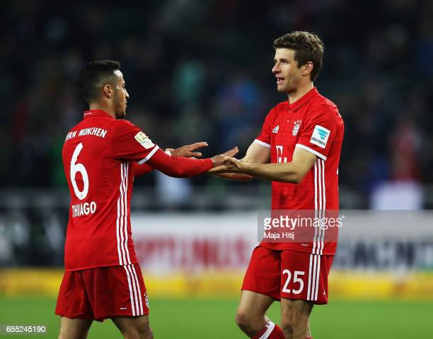Thomas Mueller of Bayern Munich celebrates with Thiago after victory in the Bundesliga match between Borussia Moenchengladbach and Bayern Muenchen at...