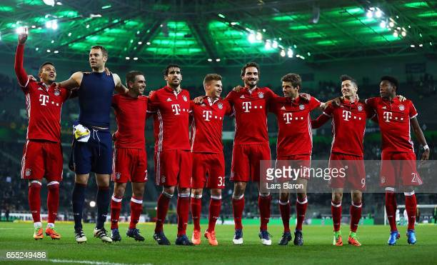 Thomas Mueller of Bayern Munich celebrates with Thiago and Manuel Neuer and team mates after victory in the Bundesliga match between Borussia...