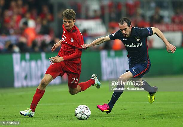 Thomas Mueller of Bayern Munich is chased by Diego Godin of Atletico Madrid during UEFA Champions League semi final second leg match between FC...