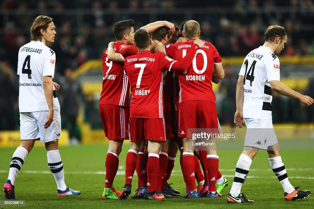 Thomas Mueller of Bayern Munich is congratulated by team mates after scoring a goal during the Bundesliga match between Borussia Moenchengladbach and Bayern Muenchen at Borussia-Park on March 19, 2017 in Moenchengladbach, Germany.