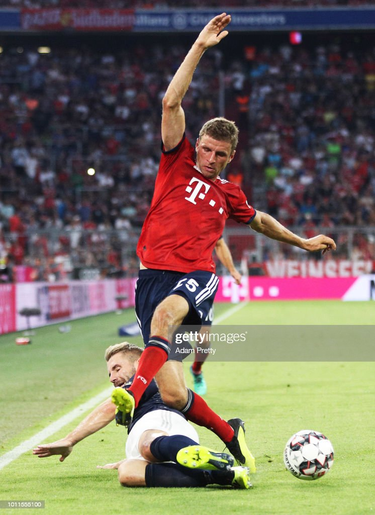 Thomas Mueller of Bayern Munich is tackled by Luke Shaw of Manchester United during the Bayern Muenchen v Manchester United Friendly Match at Allianz Arena on August 5, 2018 in Munich, Germany.