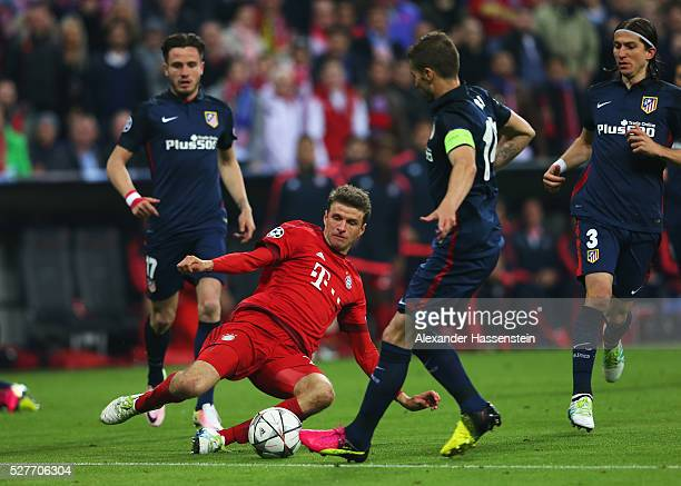 Thomas Mueller of Bayern Munich slides to tackle Gabi of Atletico Madrid during UEFA Champions League semi final second leg match between FC Bayern...