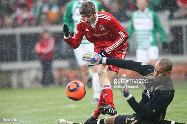 Thomas Mueller of Bayern scores the first goal against Stephan Loboue of Fuerth during the DFB Cup quarter final match between FC Bayern Muenchen and...